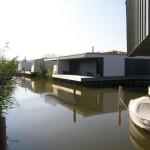 Hlavní obvodový kanál s výhledem na atriové domy v bílé barvě, pohled na řešení teras a přístup k lodím.