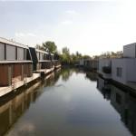 Detail atriových domů, pohled na úroveň přízemí nad vodní hladinu, na založení na pilotách, na svislé dělící paravany.