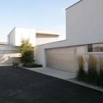 Pohled na velkorysý vstupní a příjezdový prostor atriových rodinných domů a garážová stání.