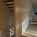 Detail jednoramenného schodiště z dřevěných stupňů bez podstupnic a ukotvení do obvodové stěny a dřevěné trámečkové schodišťové stěny.