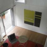 Pohled z galerie na jednací prostor atelieru, na stěnách výtvarné umění ve stylu abstraktní geometrie.