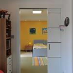 Dětské pokoje mohou být odděleny posuvnými dveřmi. Prozatím však mají děti společné zájmy a prostor užívají dohromady.