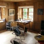 Obývací prostor s TV a malým pracovním koutem v historické části budovy. Obkladové řešení celé místnosti je v dřevěném neorenesančním stylu. Kontrastním doplňkem jsou světoznámé kovové židle od firmy Knoll.