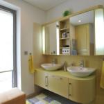 Dětská koupelna je navržena ve žlutých odstínech podobně jako jejich pokoje.