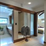 Mezi ložnicí manželů a jejich koupelnou byla navržena velkorysá šatna. Protože se tudy prochází, jsou oděvy schované ve vestavěných skříních navržených na míru prostoru.