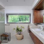 Do koupelny si manželé přáli umístit prostorný sprchový kout. Bílá keramická umyvadla zasazená do světlé kamenné desky z quarelly barevně vyvažuje nábytek z dýhy ořechu.
