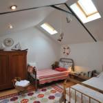 Dětský pokoj v horním patře zahradního domku. Mosazné postele se hodí do celkového charakteru stavení.