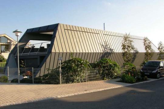 Architekt se musel při návrzích striktně držet mnoha omezujících regulativů. Jedním z nich byla i sedlová střecha. Všimněte si, jak se s omezením vypořádal a za zamyšlení stojí i postoj místních úřadů.