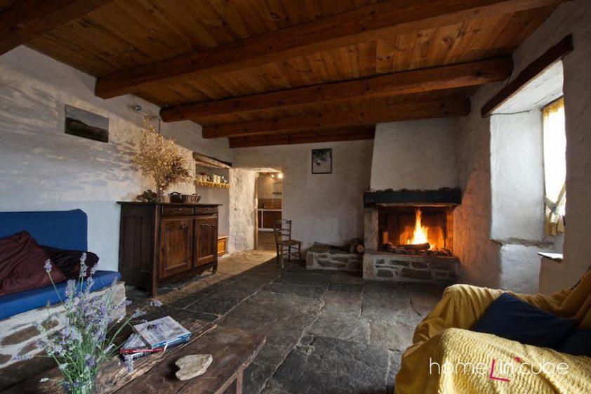 Kamenné podlahy i zdi pocitově zatepluje dřevěný strop. K útulné atmosféře přispívá i krb s otevřeným ohněm.