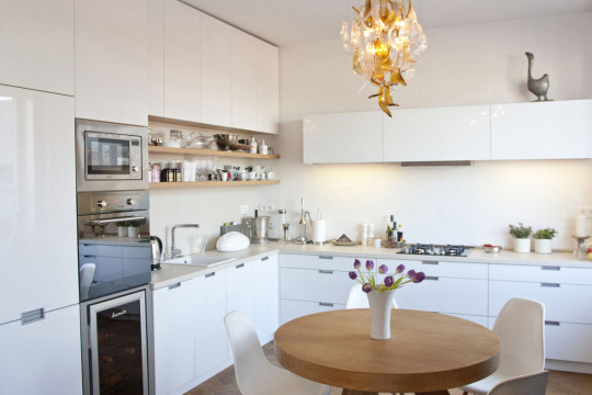 Do nevelké kuchyně navrhla architektka kuchyň přes dvě obvodové stěny. Tím dosáhla dostatečně velkého pracovního místa. Zbyl prostor i na jídelní stůl, jehož kulatý tvar je v tomto případě ideálním řešením.