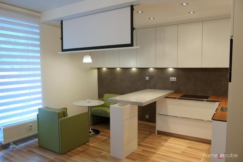 Kuchyň je od sezení pro dva oddělena barovým pultem. V podhledu je schované plátno na promítání.