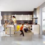 Pro velkou rodinu bude ideální uspořádání kuchyně Primo značky Nobilia, která má kromě řady horních a dolních skříněk uspořádaných do tvaru písmene L ještě středový ostrůvek a na něj navazující jídelní pult. Prosklená zástěna opticky dělí místnost na kuchyň s jídelnou a obývací pokoj.