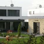 Detail zahradního prostoru, přechod z interiéru obývacího prostoru do exteriéru a fasádní řešení jednotlivých hmot, bílá omítka versus kamenný kvádříkový obklad.