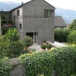 Viditelný jasný kontrast šedivého betonového fasádního systému a syté zeleně.