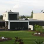 Tří hmotový systém uspořádání domu, bezpečnostní uzavření interiéru domu svinovacími žaluziemi a elegantní řešeni zahrady ve stylu golfového hřiště.