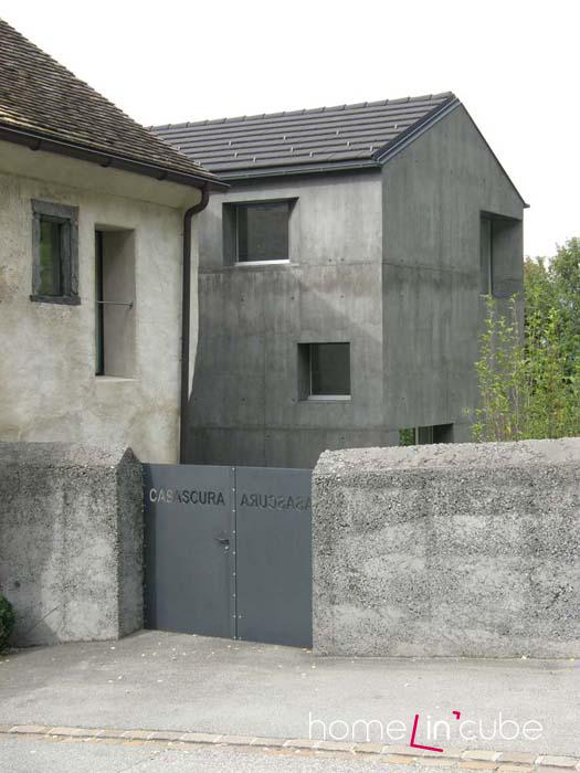 Plné betonové oplocení je v souladu s tmavým domem. Beton nádherně doplňují ocelová vrata ozdobená názvem ateliéru.