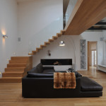 Výrazným prvkem interiéru je schodiště. Aby dokonale vynikla jeho linie, byl do zdi ukotven plech, který byl následně obložen dřevem. Zábradlí je vyrobeno z čirého skla, které přesně kopíruje linii schodů.
