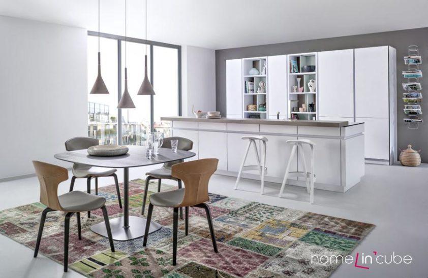 V kuchyňských policích už nemusíte mít pouze nádobí, spotřebiče a kuchařské knihy, klidně si vystavte i umění a věci, které jsou obvyklé třeba pro obývák. Nová kuchyň značky Leicht v matném bílém provedení.