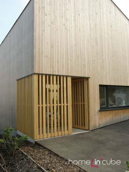 Hlavní vstup z ulice má praktické zádveří, jehož provedení ladí s dřevěným fasádním systémem.