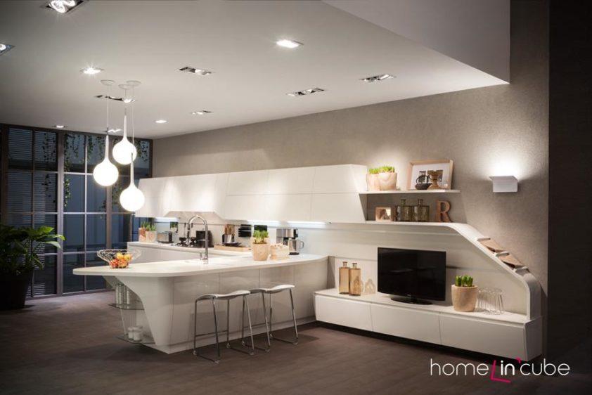 """Novinkou značky Scavolini je futuristická kuchyň FluxSwing, jejíž celý jeden modul tvoří v levé části kuchyň a v pravé části obývací stěnu. Jídelní a pracovní místo řeší ostrůvek vklíněný do středu """"stěny""""."""