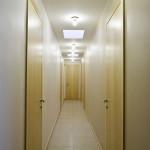 """Hned za vstupem je možno mimo jiné také vejít do chodby, které majitelka říká """"hotelová"""". Za dveřmi se nacházejí ložnice a koupelny."""