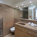 Nevelká koupelna je díky použití jednoho typu kamene opticky sladěna.