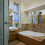 Na míru vyrobený podstavec pro vanu doplněný deskou z přírodního kamene, který je použit i na podlaze a stěnách koupelny.