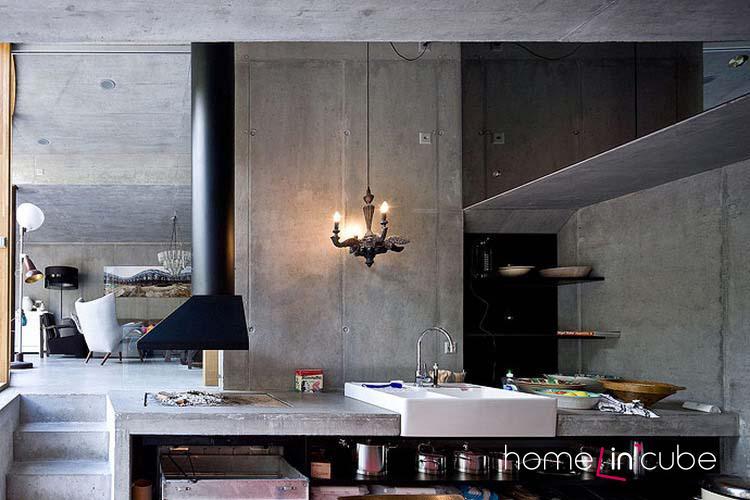 Betonové prvky se odrážejí i v interiéru. Studený materiál je okořeněn ostatními doplňky. V kuchyni se vaří i na otevřeném topeništi.