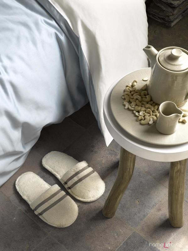 Trojnožka místo nočního stolku. Dřevěné nožky dodávají útulný podtext místnosti.