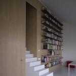 Na hladkém dřevěném obkladu stěny vynikají vodorovné linie polic knihovny.