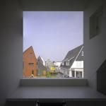 Detail pracovny a pracovního stolu, velký horizontální střešní vikýř s pevným bezrámovým zasklením, průhled do hlubší perspektivy exteriéru okolní zástavby.