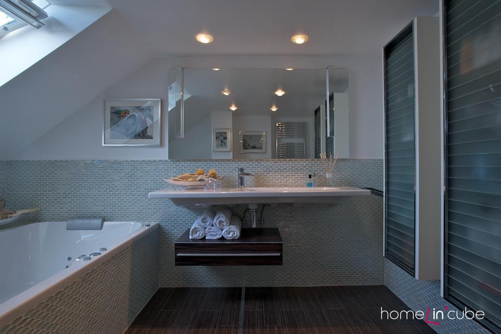 Členitost prostoru koupelny je podtržena vodorovnou linií velkorysého umyvadla.