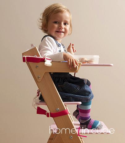 Snadno smontovatelná dřevěná židlička Sedees s nastavitelnou výškou sedáku a opěrky nohou má odnímatelnou jídelní desku.