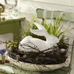 Soška zajíčka osazena do hnízda z proutí, ozdobeného jarními květy a kraslicemi jsou symbolem jarních svátků Velikonoc.
