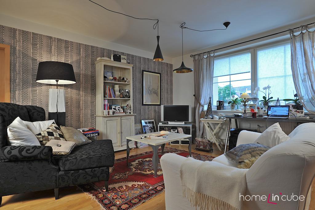 Bílá a odstíny šedé v interiéru, doplněné barevným kobercem, je sázka na jistotu.