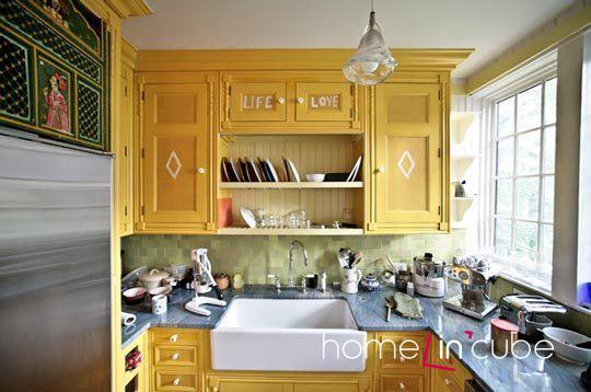 Žlutý odstín skříněk lze na stěnách a podlaze dobře kombinovat s neutrálními světlými ale i kontrastními tmavými barvami.