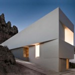 Dům v podobě šedobílého krystalu jakoby ze skály vyrůstal.