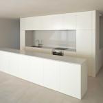 Kuchyně s bílou lakovanou úpravou, podlaha je tvořena velkoformátovou dlažbou ze světlého mramoru.
