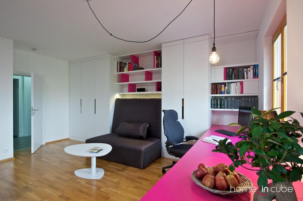 Po celé délce jedné stěny je prostorný pracovní stůl, na který navazuje knihovna.