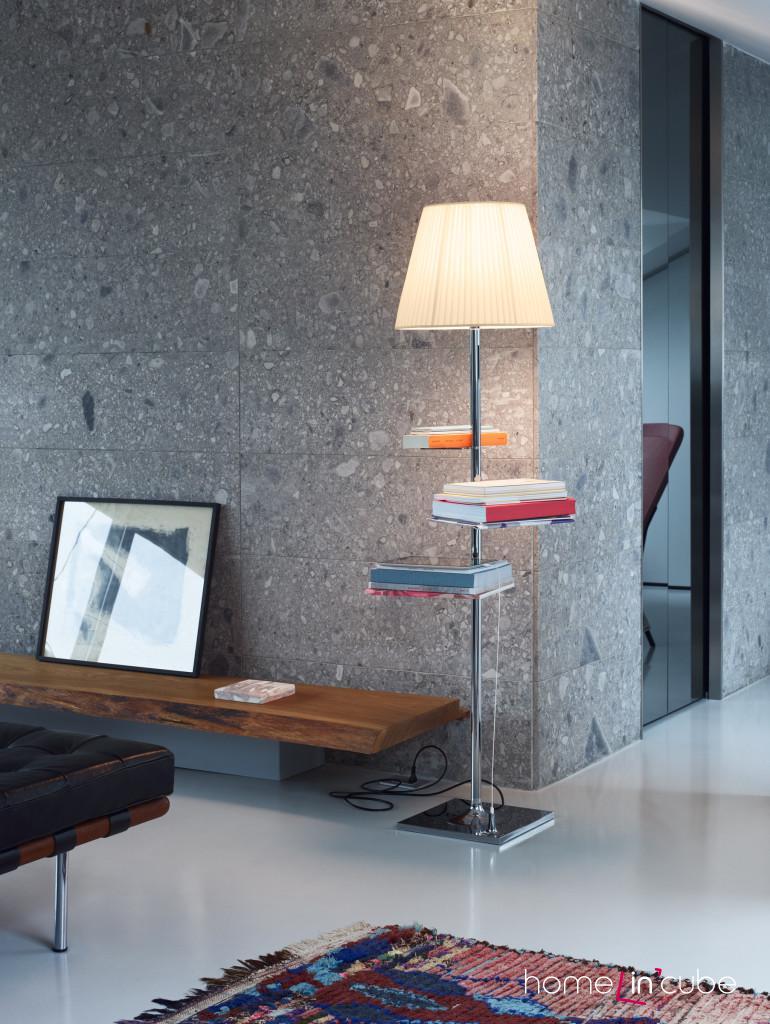 Stojací lampa na jejímž těle jsou přichyceny ještě tři malé stolky. Flos. Prodává Uni light.