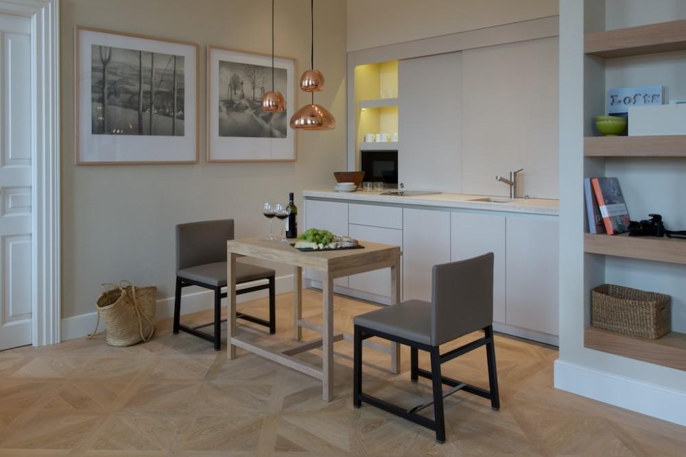Aby kuchyně výrazně nevyčnívala, je navržena do niky, která byla kvůli ní speciálně vytvořena. Úložný prostor je schován za posuvnými dvířky.