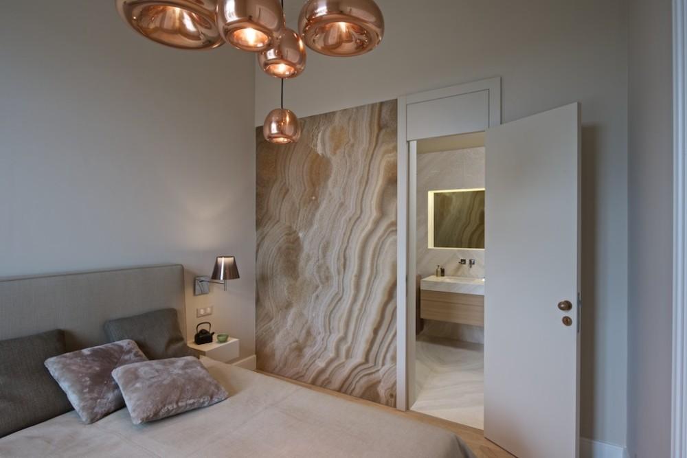 Stěnu mezi ložnicí a koupelnou zdobí deska z onyxu.