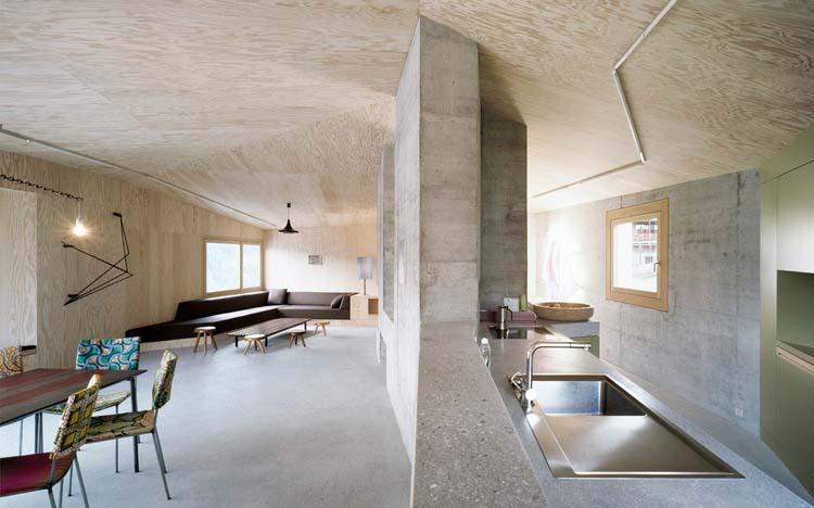 Širokoúhlý pohled do hlavních obytných prostorů. Obývací prostor s jídelnou a podélná kuchyně, svislé stěny z pohledového betonu, podlahová plocha z broušeného cementového potěru, podkrovní podhled a svislé obkladové konstrukce z překližky.