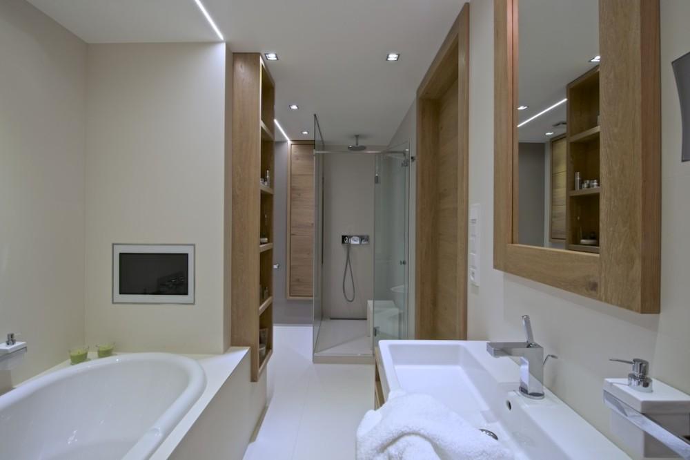 Ve stěně u vany je koupelnový televizor.