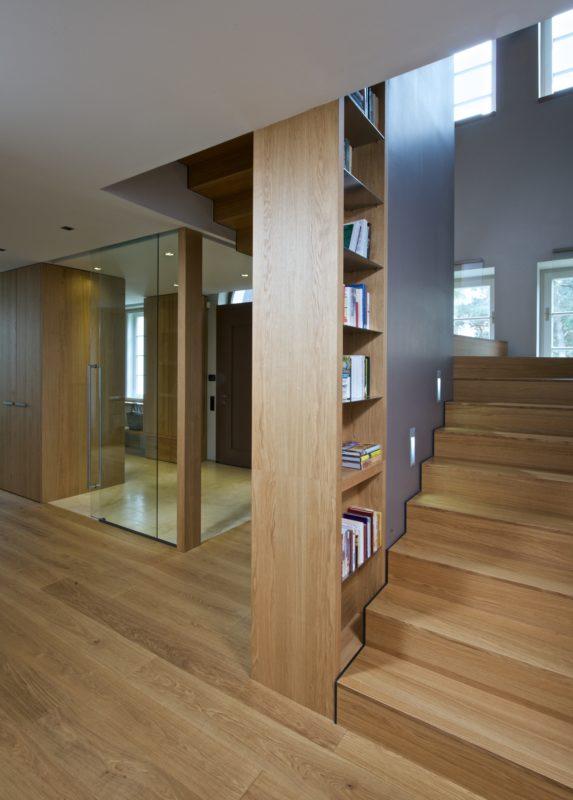 Kolem schodiště jsou navrženy otevřené police. Majitelé je proměnili na knihovnu.