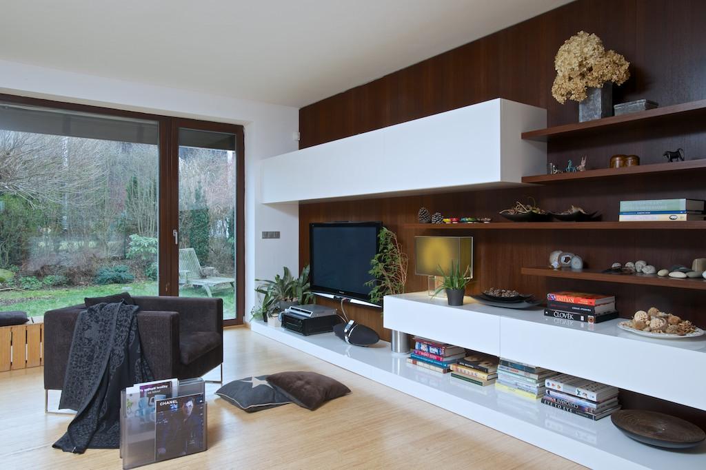 Obývací stěna je vyrobena na míru prostoru a je navržena na stěnu, která stojí přímo proti velké knihovně s krbem.