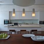 Bílá kuchyně zvýrazňuje stůl a židle z masivu.