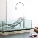 Skleněná vana je doplněná ergonomicky tvarovaným lehátkem.