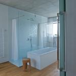 Sprchový kout walk in vymezuje mozaika ve světlých odstínech.