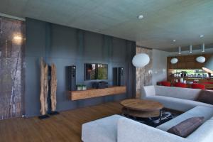 Jedna ze stěn je obložena plechovými díly. Industriální vzhled zjemňují dřevěné prvky.